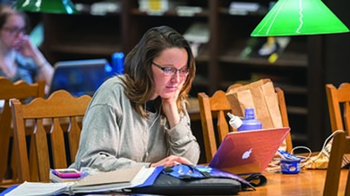 A student in the library working on a computer
