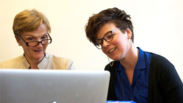 Peggy O'Neill works with a student on a computer